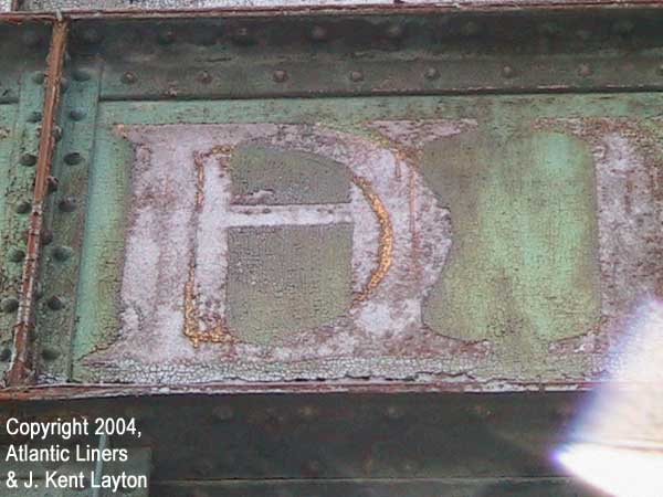 Extreme closeup of lettering on pier building's front. Easily legible is the D from Cunard and the