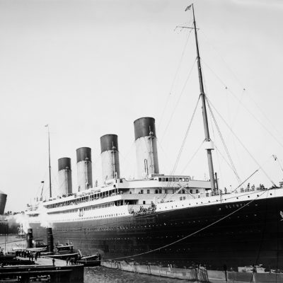 The Olympic pulling up to her Manhattan pier at the end of her maiden voyage. Behind her, the Lusitania is pulling out of Pier 54 to begin an eastward crossing, (Library of Congress, J. Kent Layton Collection)